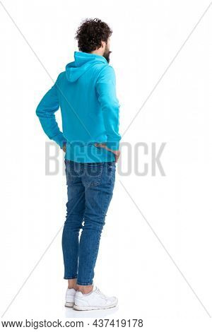 bearded young man in hoodie holding hands on hips and waiting in line on white background in studio, full body