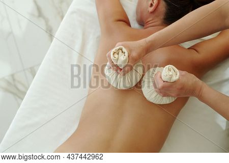 Hands of young masseuse touching back of relaxed female client of spa salon with two herbal compress balls