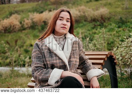 Pensive, Thoughtful Young Woman In Coat Sitting Alone On Wooden Bench. Sad Woman Daydreaming, Thinki