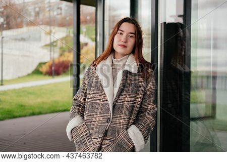 Pensive, Thoughtful Young Woman In Coat Standing Alone Looking At Camera. Daydreaming Woman, Thinkin