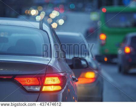 Cars waiting for street light in rush hour traffic jam on dusk busy city street. Shallow DOF, focus on red tail lights.