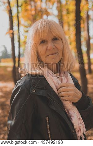 Senior Woman Enjoying Autumn In Park. Active Aging And Senior Female Concept.