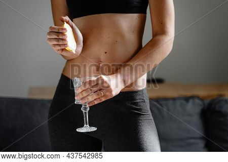 Close Up Of Young Fit Slim Woman Preparing Water With Lemon Juice. Morning Ritual. Healthy Antioxida