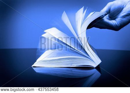 Book for reading and hand flipping pages looking at information