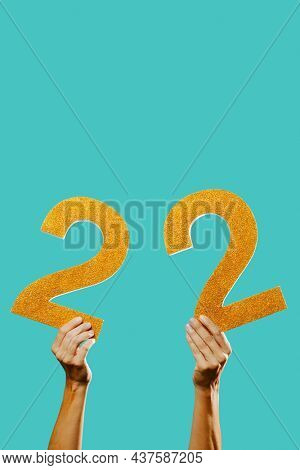 closeup of a man holding two golden three-dimensional numbers forming the number 22 on a blue background, with some blank space on top