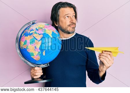 Middle age handsome man holding paper plane and world ball smiling looking to the side and staring away thinking.