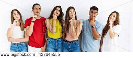 Group of people wearing casual clothes standing over isolated background with hand on chin thinking about question, pensive expression. smiling with thoughtful face. doubt concept.