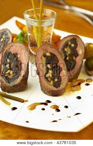 Beef rolls with prunes, cheese and pine nuts