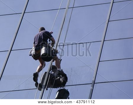 man cleaning windows on a high rise building poster