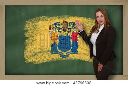 Successful beautiful and confident woman showing flag of new jersey on blackboard for marketing research presentation and tourist advertising poster