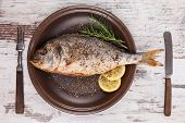 Grilled barbeque sea bream with lemon and rosemary on brown plate with antique cutlery isolated on white wooden textured background. Mediterranean seafood background. poster