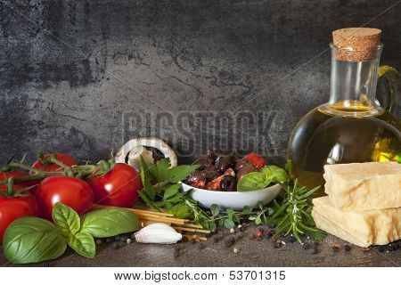 Italian food background, with vine tomatoes, basil, spaghetti, mushrooms, olives, parmesan, olive oil, garlic, peppercorns, rosemary, parsley and thyme.