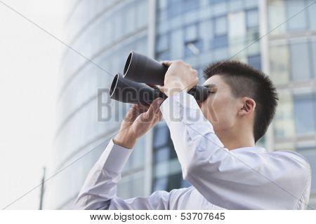 Young businessman looking through binoculars