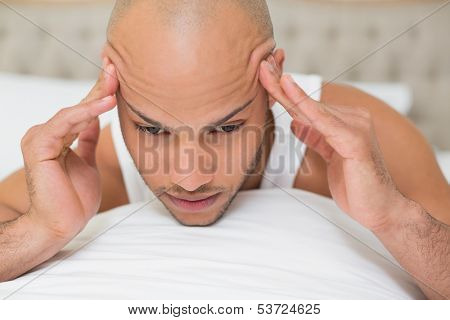 Young bald man suffering from headache in bed at home poster