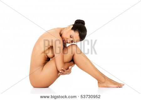 Attractive naked woman sitting. Side view. Isolated on white.