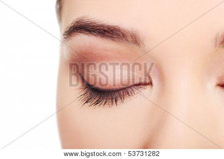 Close up on female's face- eye. Isolated on white.