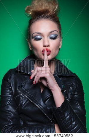 young woman in leather jacket with eyes closed making the silence sign