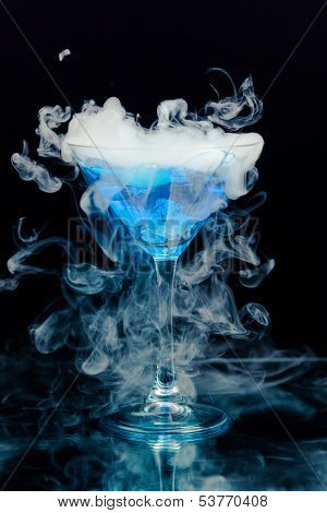 blue cocktail with splash and ice vapor