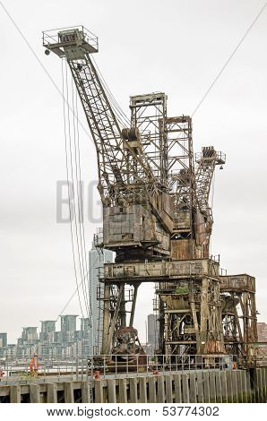Two cranes used to haul coal from barges on the River Thames at the disused Battersea Power Station.  The structure is about to be redeveloped.  Wandsworth, London. poster