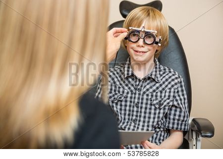 Female optician determining prescription values with optometric frame for boy in store