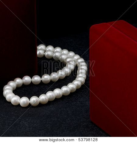 Pearl necklace lies near a red box on a black background. poster
