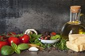 Italian food background, with vine tomatoes, basil, spaghetti, mushrooms, olives, parmesan, olive oil, garlic, peppercorns, rosemary, parsley and thyme.   poster