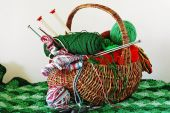 Closeup of handmade wicker basket filled with yarn thread knitting needles and sewing supplies setting on a knitted green afghan. Isolated on neutral background. poster