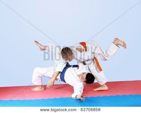 Sportsman with an orange belt threw athlete with a blue belt