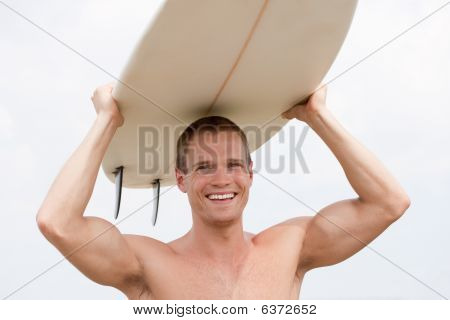 Fit Youn Man With Surfboard