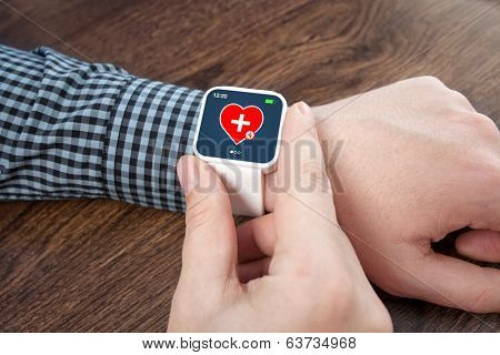 Male Hands With White Smartwatch With Mobile App Health Sensor On The Screen