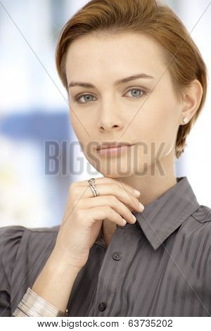 Portrait of attractive thinking businesswoman looking at camera, hand on chin.