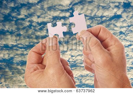 Two hands in silhouette against white blue clouds connect jigsaw puzzle pieces poster