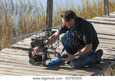 man preparing helicopter drone for takeoff