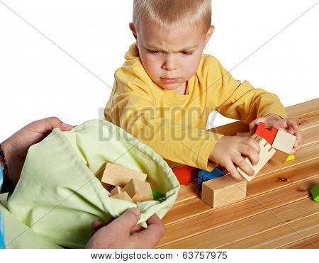 Little boy is upset while packing away wooden blocks. his father is helping him. isolated on white