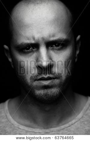 Vertical portrait of spiteful man looking at camera