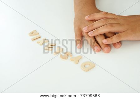 Hands Of A Girl Form The Word Dyslexia With Wooden Letters