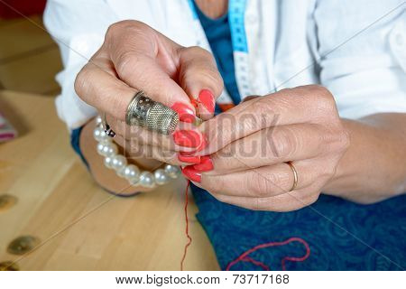 A Woman Threader The Wire In A Needle