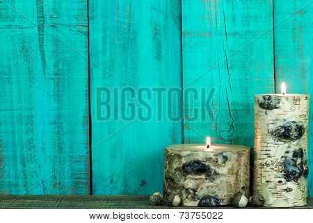 Textured log candles burning by antique green background