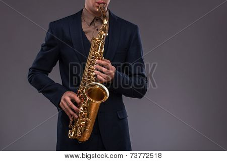 Close-up picture of a trumpet in hands of a jazz man in a suit playing on it with enthusiasm isolated on grey background with copy place, concept of jazz music poster