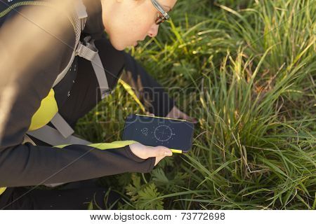 Woman With Backpack geocaching With Digital Compass