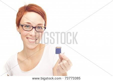 Smiling casual redhead woman holding SD Card