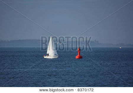 White Yacht approaching a Red Buoy