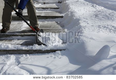 Man shoveling the snow on  bright winter day