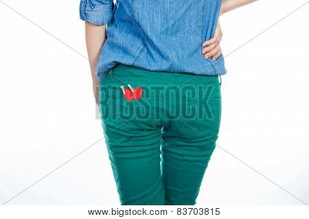woman in a blue denim shirt and green jeans standing isolated on white background with a red paper