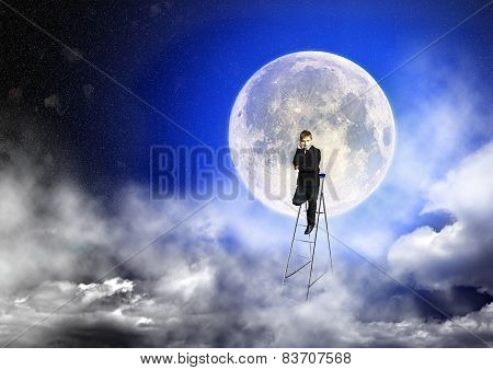Boy In Suit Stands On A Step-ladder Against The Background Of A Full Moon
