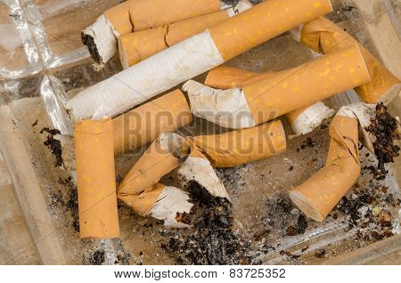 Many filter cigarette butts filling a small ashtray poster