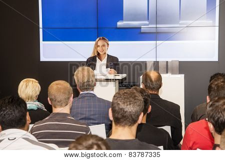 Young Woman At The Lectern In Front Of Audience