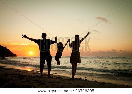 Happy Family Playing At The Beach In The Dawn Time