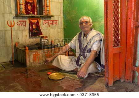 VARANASI, INDIA - 20 FEBRUARY 2015: Holy man sits on ground in small temple and waits for pilgrims.