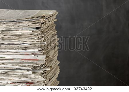 A Pile Of Newspapers On A Dark Background